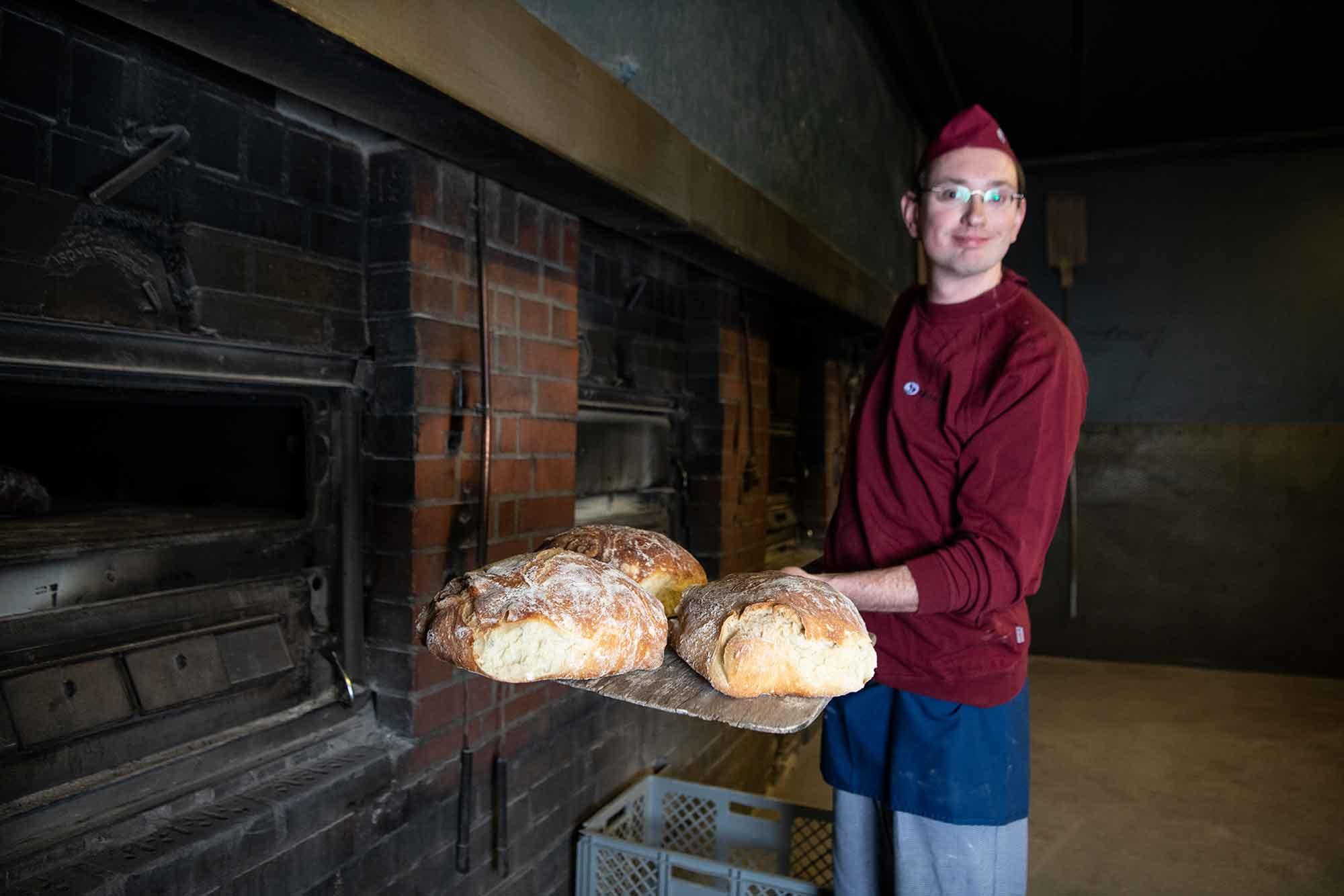 Bäcker mit Brot vor Holzofen